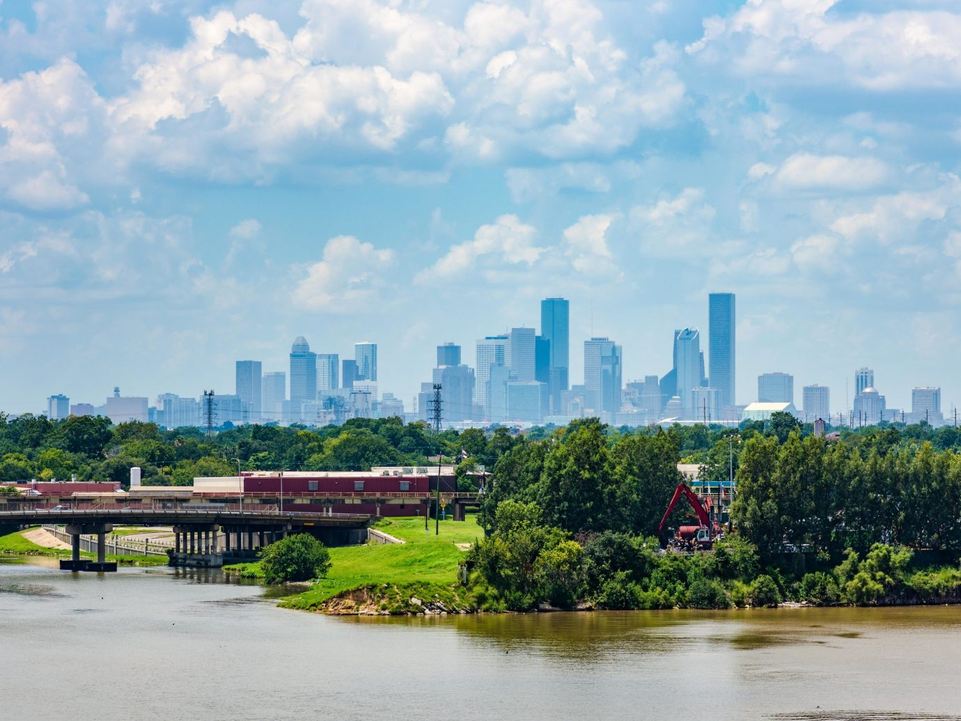 Houston Outdoors + Adventure Texas Trip Ideas metropolitan area skyline City daytime cityscape sky urban area skyscraper reflection water River metropolis tree bank Downtown tower block cloud water resources horizon landscape grass