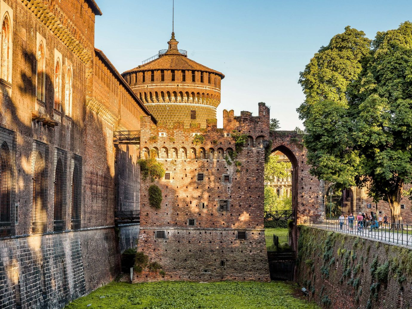 Arts + Culture Italy Milan Nature wall landmark historic site sky medieval architecture château fortification castle Town history tree tourist attraction ancient history stately home building middle ages City facade tourism estate tours palace plant moat arch