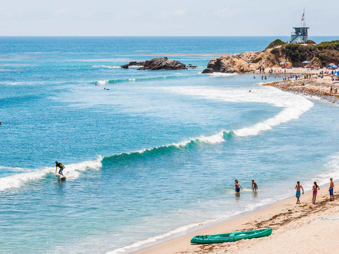 Surfers, swimmers, and sunbathers enjoying the ocean at Leo Carrillo State Beach in Malibu, California.