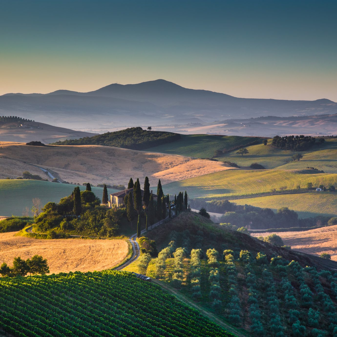 Scenic Tuscany landscape with rolling hills and valleys in golden morning light, Val d'Orcia, Italy.
