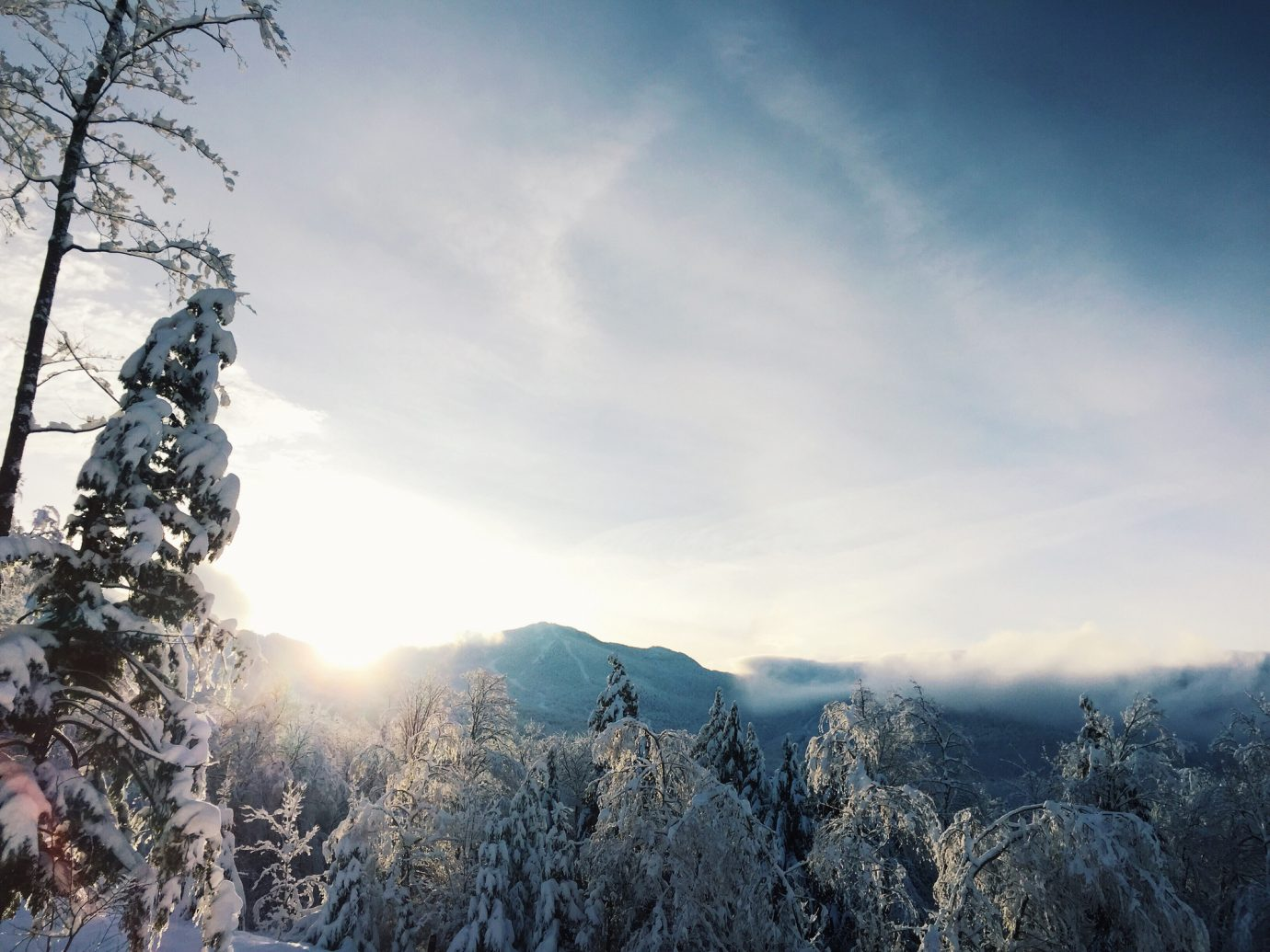Looking eastward toward the mountains near Smuggler's Notch in Vermont in wintertime. The sun is rising and partially visible as it crests the hills. The trees are covered in hoarfrost.