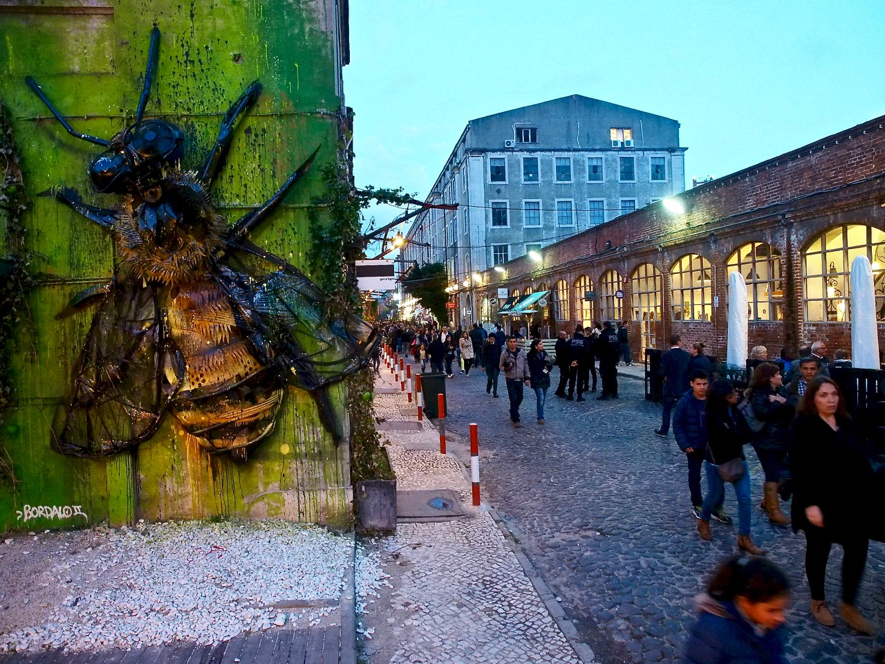Wall art with large bumble bee and a street with tons of people at dusk at LX Factory