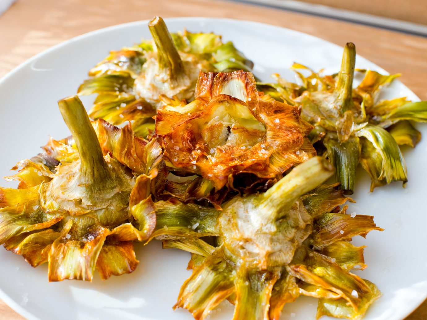 Roman fried artichokes (jewish style) with flakes of sea salt on a wooden table.