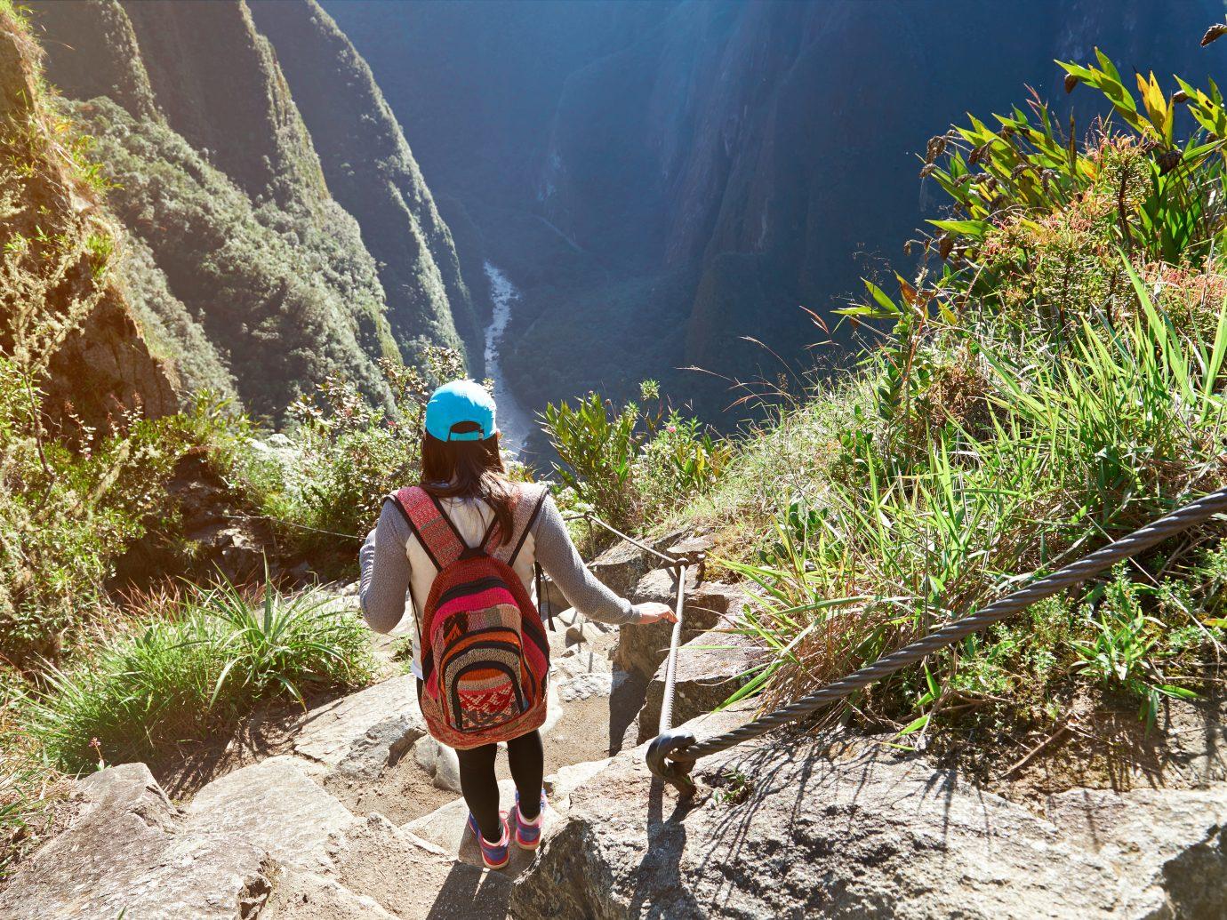 Woman in nature adventure walk in mountain landscape. Girl doing trekking in Machu Picchu path