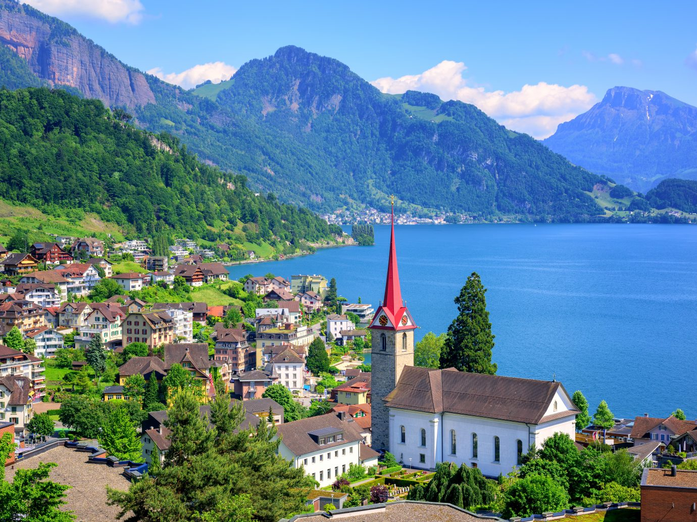 Little swiss town with gothic church on Lake Lucerne and Alps mountain, Switzerland