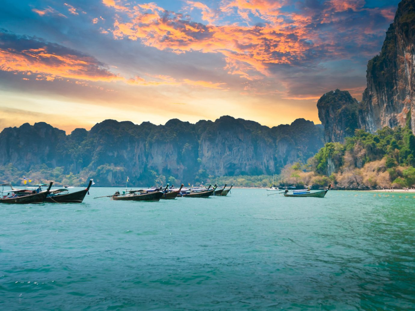 Beautiful sunset at tropical sea with long tail boat in south thailand