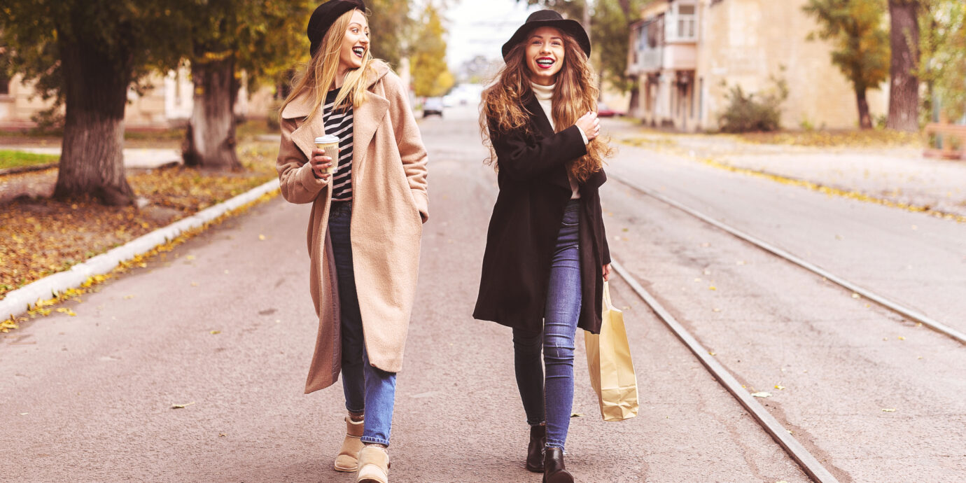 Two beautiful women walking down the street after shopping and drink coffee