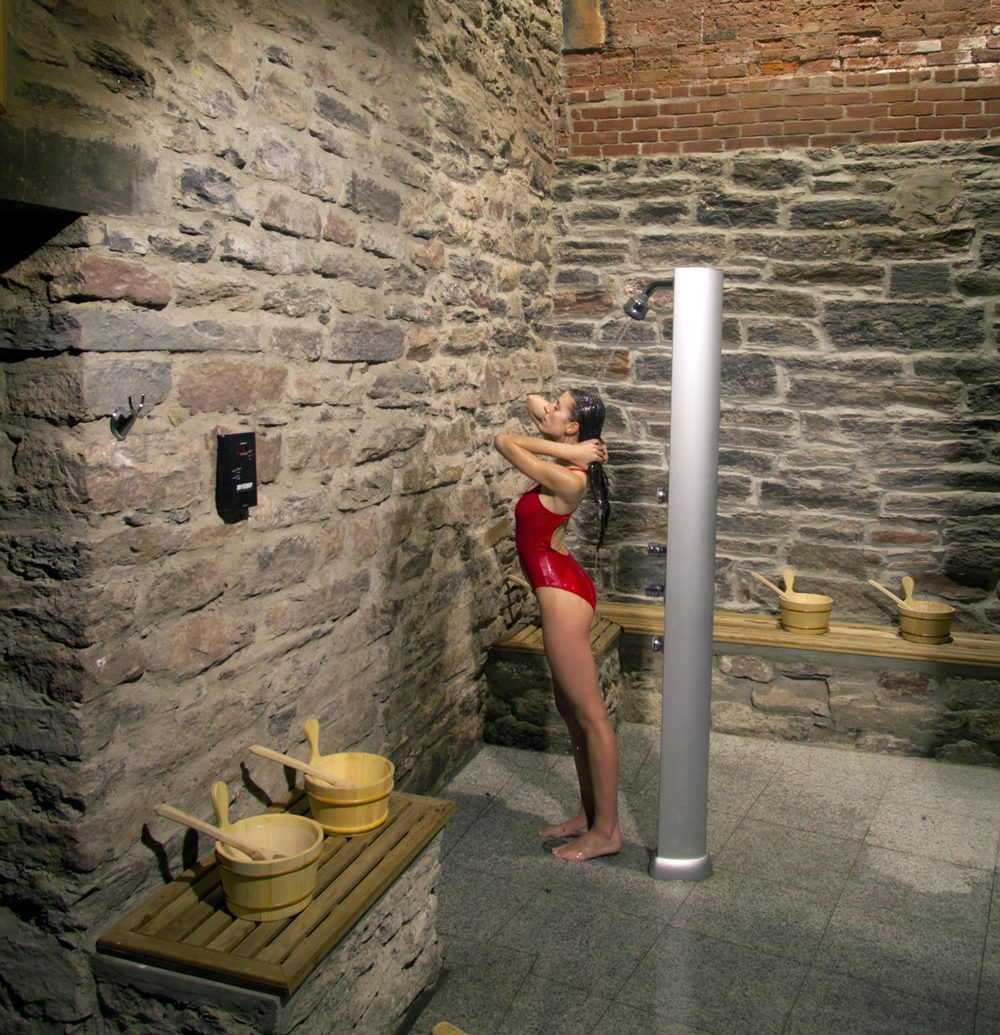 Crop of Woman showering in red bathing suit with ancient Roman wall decor at Great Jones spa