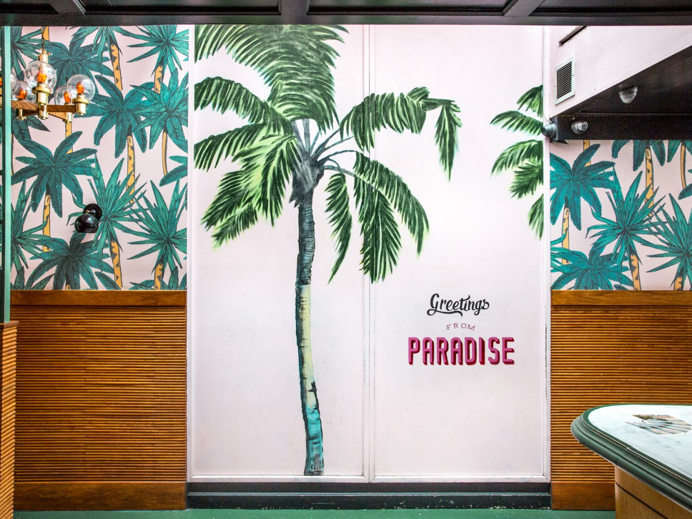 "Door with writing ""Greetings from Paradise"" with palm tree decal at The Happiest Hour in NYC"