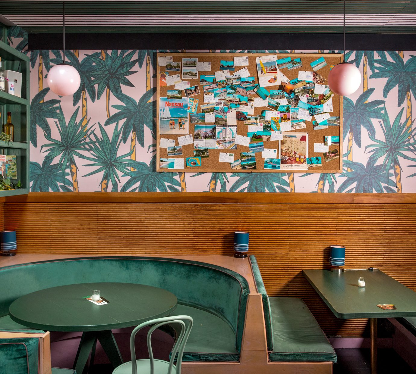 Round table booth with eccentric green tropical decor at The Happiest Hour in NYC