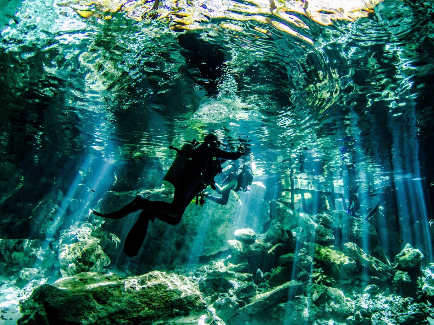 diver in blue waater of a cenote