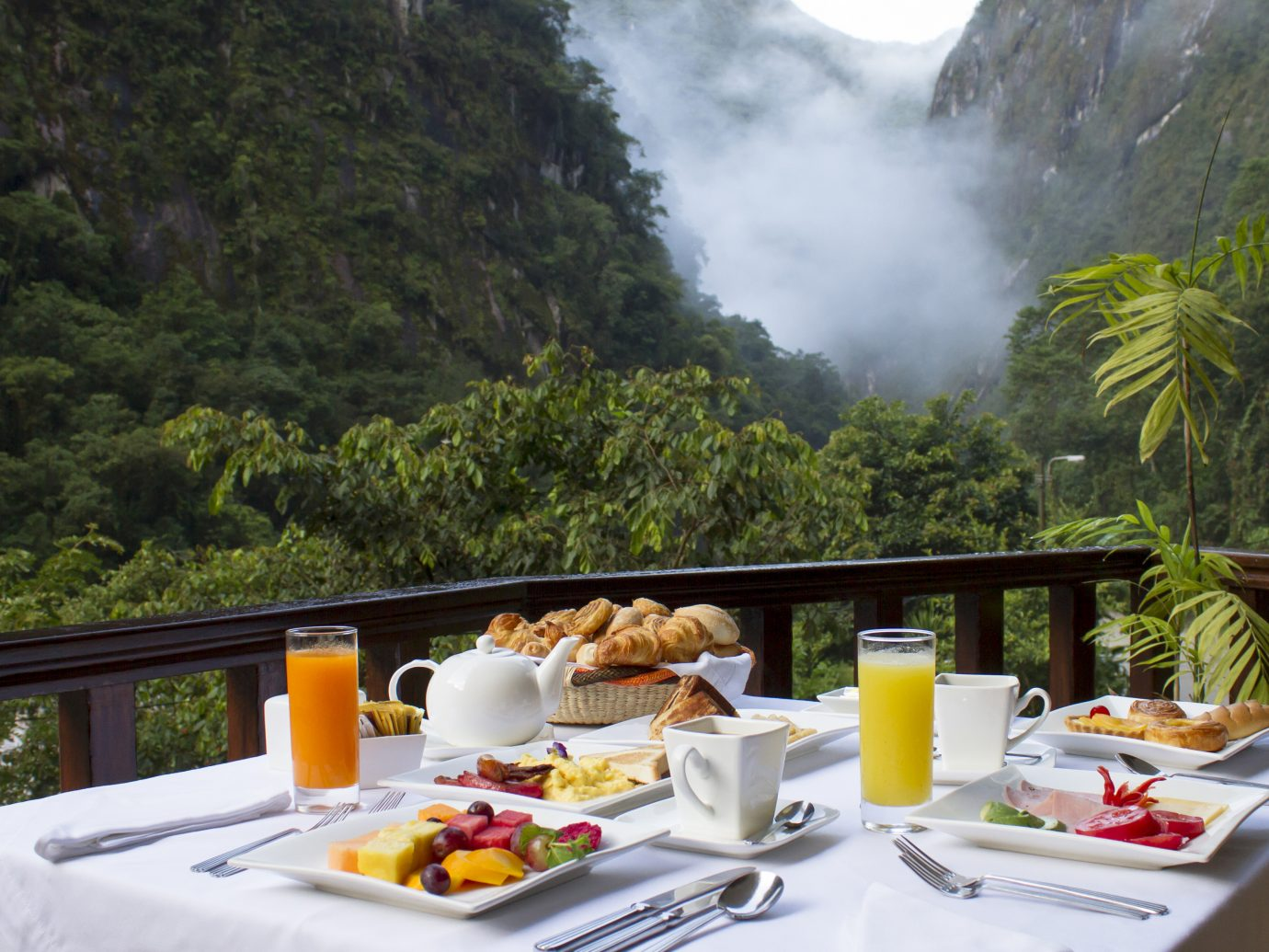 Beautiful breakfast with fruit juices, fruit and pastries overlooking steamy, lush mountains at SUMAQ