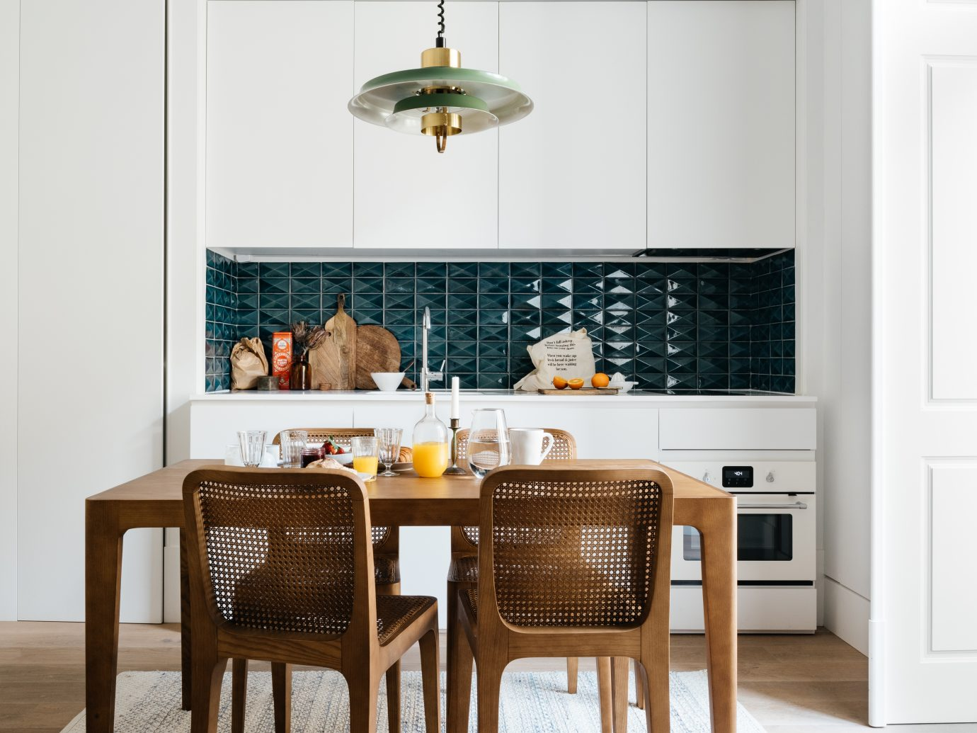 Kitchen interior with basket chairs, a set breakfast on the table, and teal tiling with white cabinets