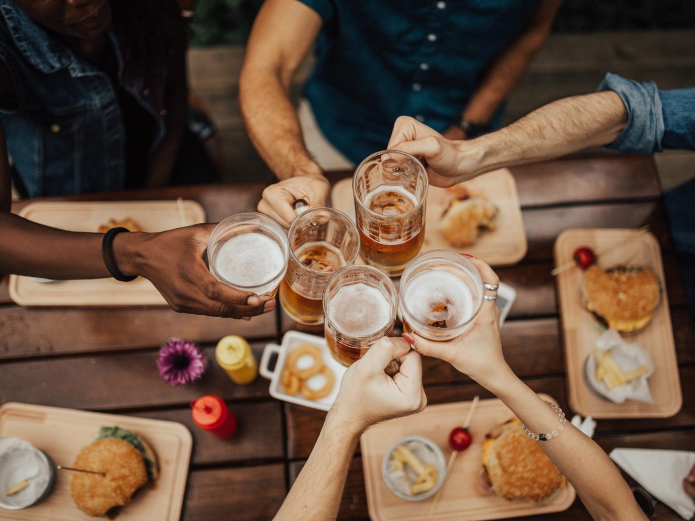 Group of friends toasting their beers with burgers on the table