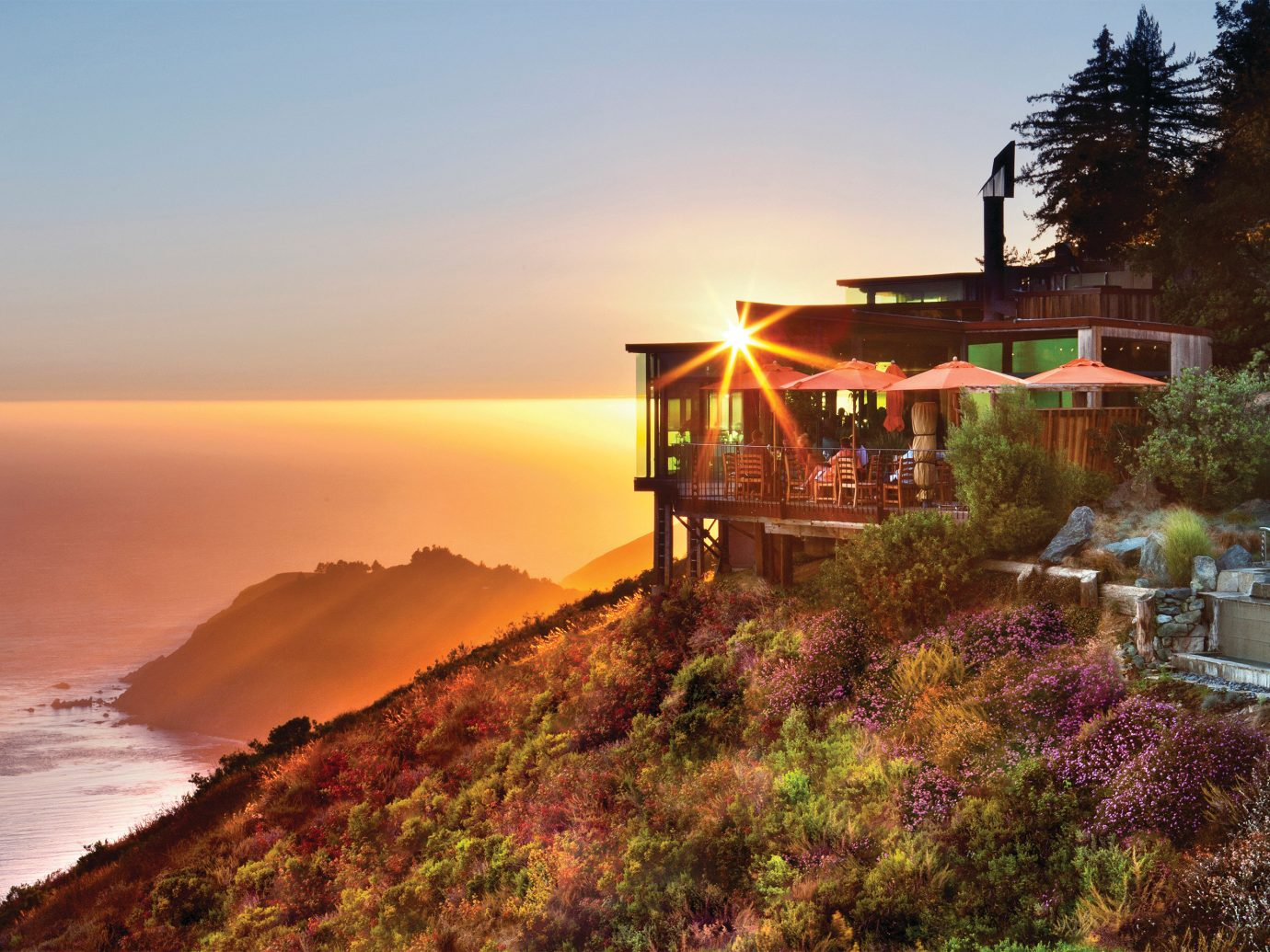 view of Post Ranch Inn perched on a cliff over the ocean during sunset