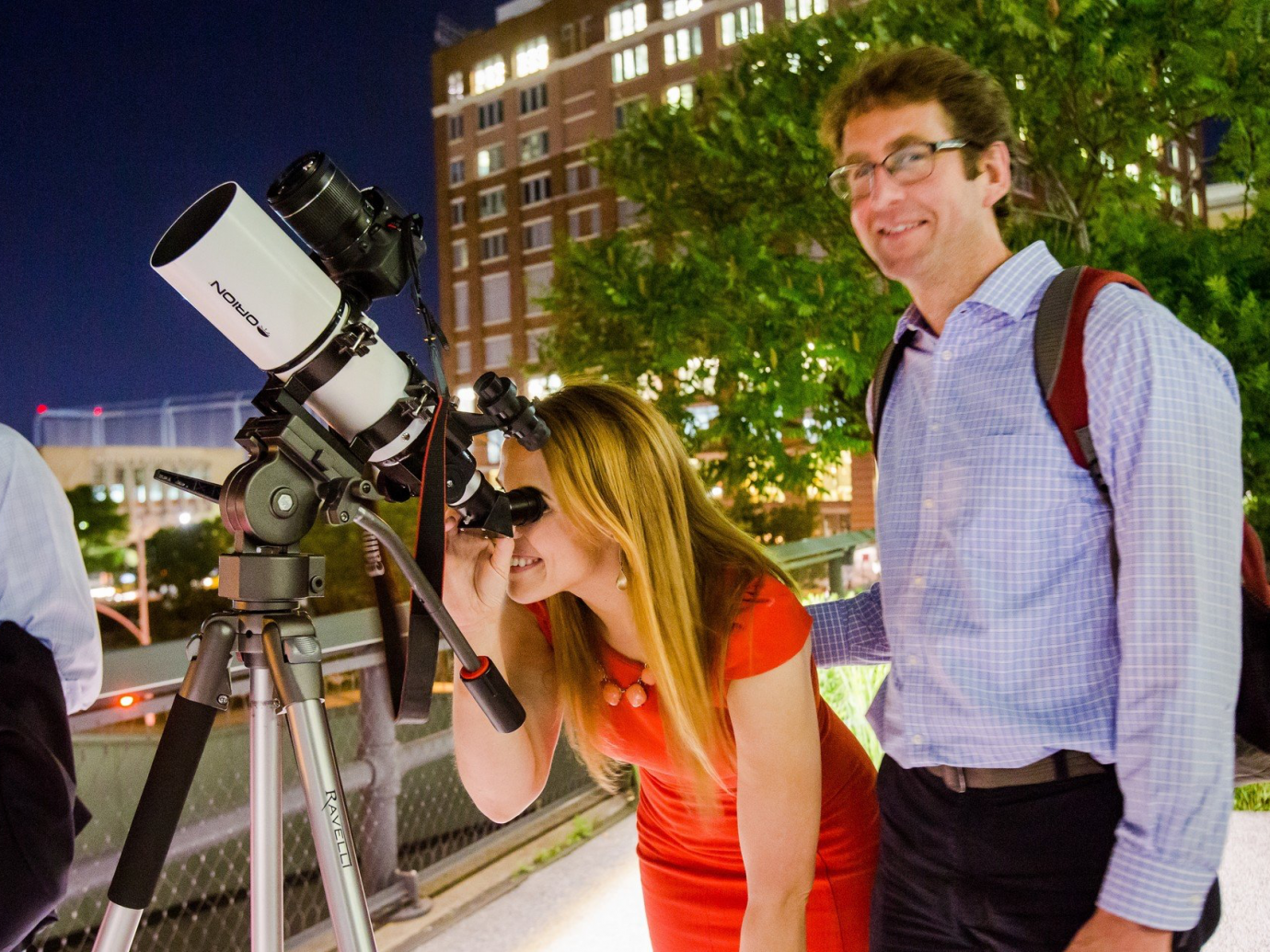 A man and woman using a telescope at night at The High Line in NYC