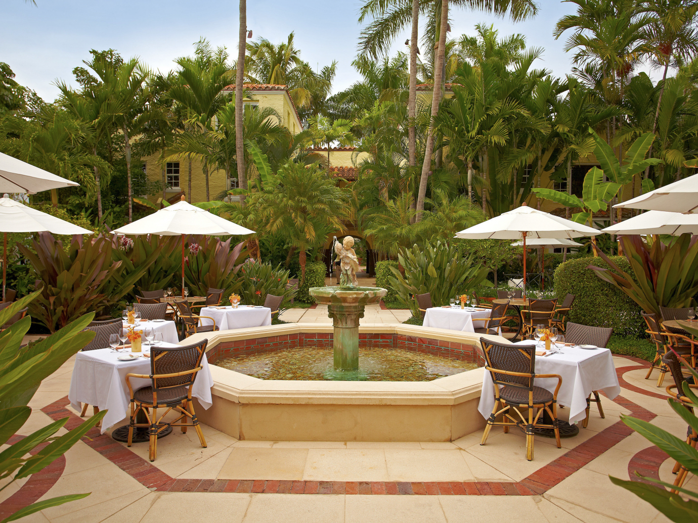 Courtyard with stone cherub holding fish spewing water into a center fountain including set tables surrounding at The Brazilian Court Hotel