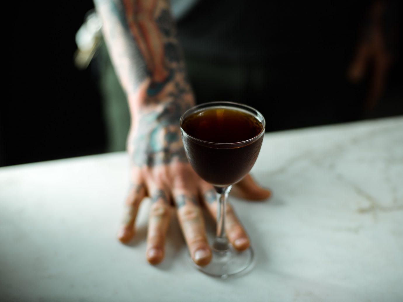 Black Manhattan cocktail served by tattooed arm