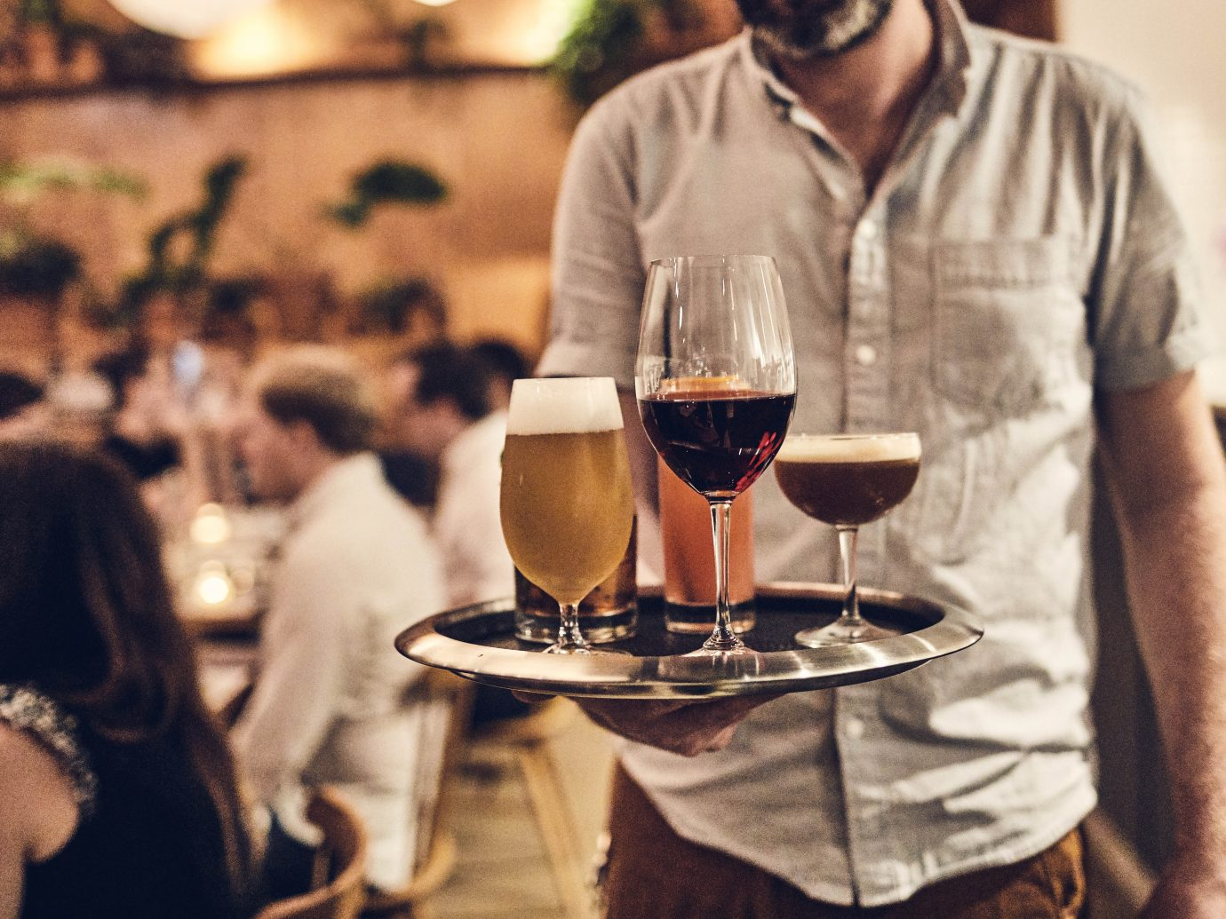 Serving walking to table in packed restaurant interior with tray of drinks