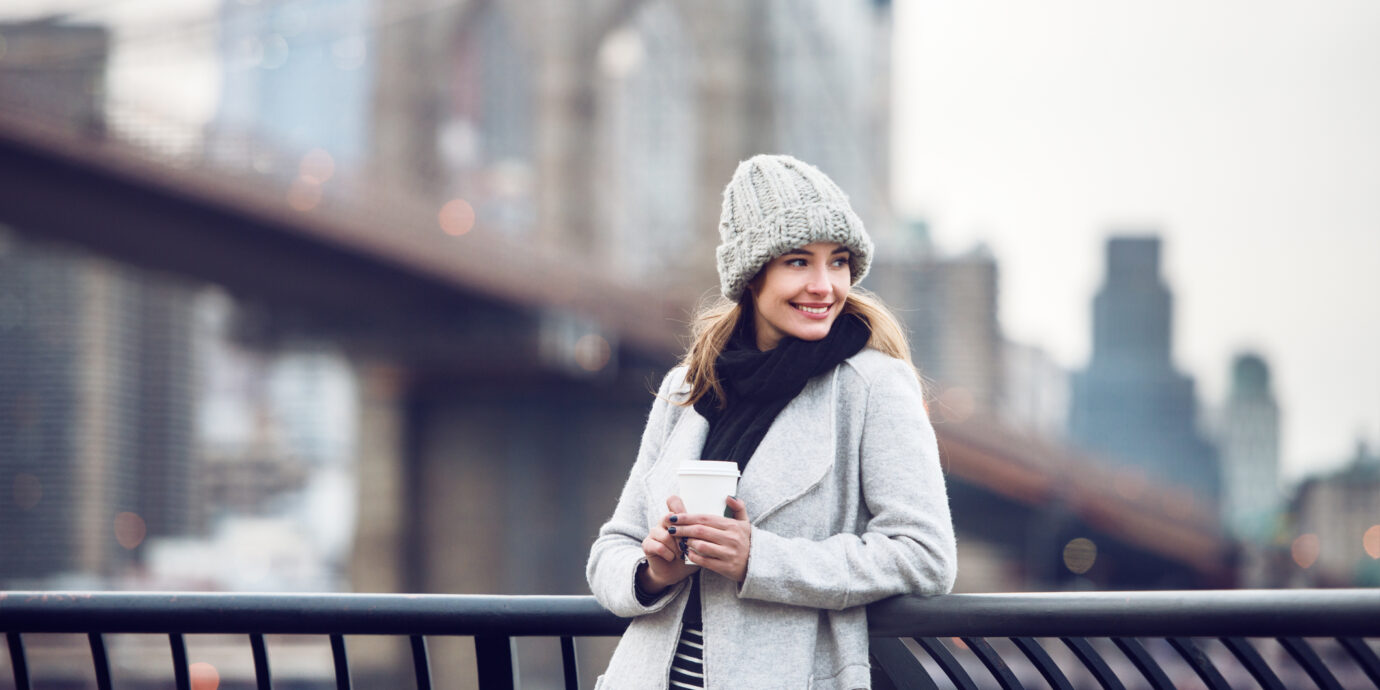 Happy smiling adult tourist woman holding paper coffee cup and enjoying the New York City view and Brooklyn bridge