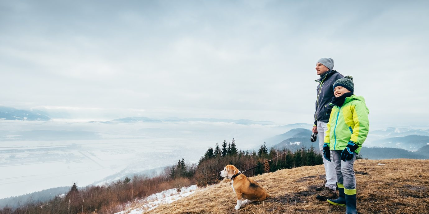 Early spring time - father with son walk with dog on mountain hills