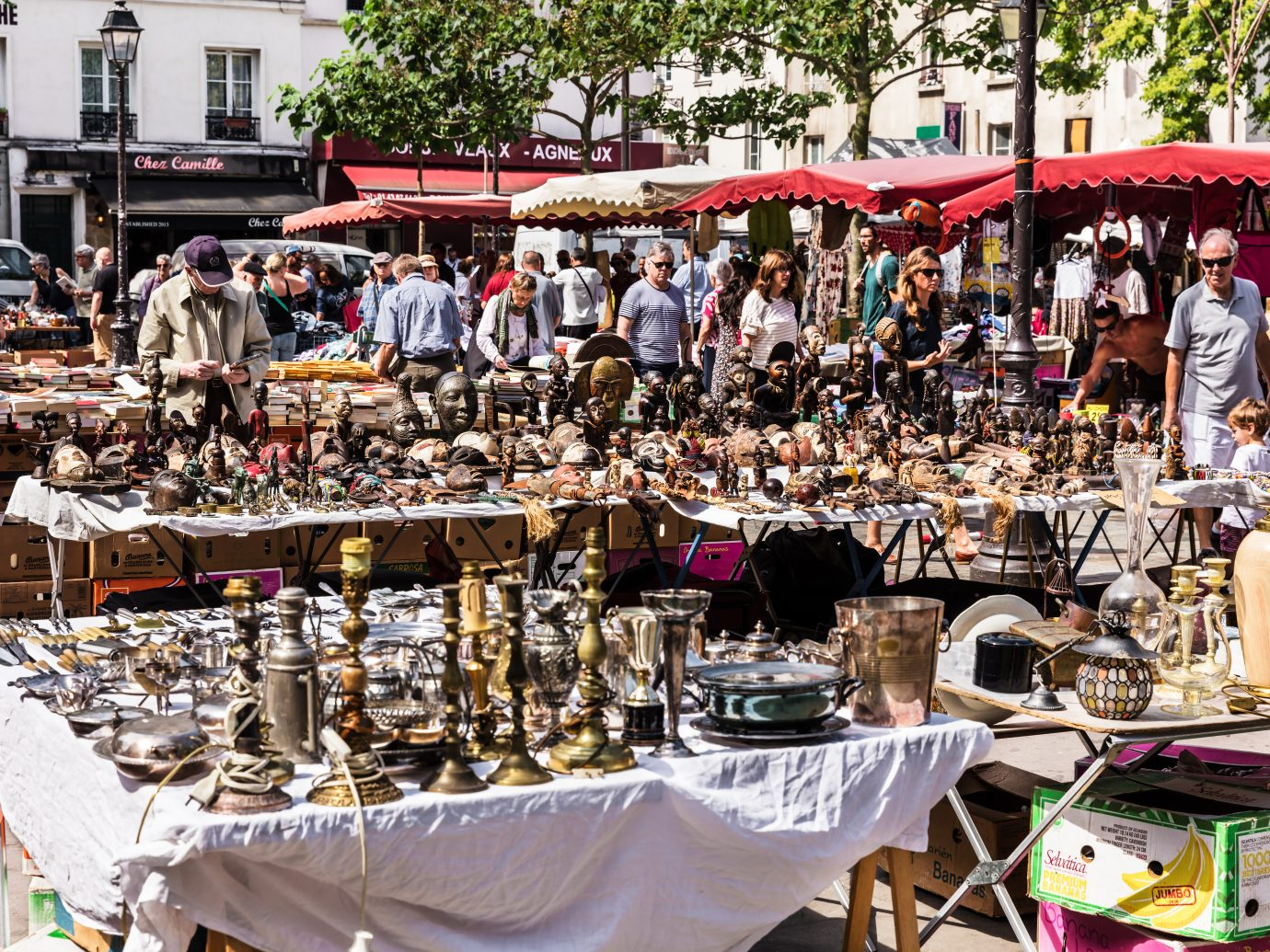 People choosing rare and used books, wooden masks and figures of African culture at the historic flea Aligre Market (Marche d'Aligre) in the Bastille district.