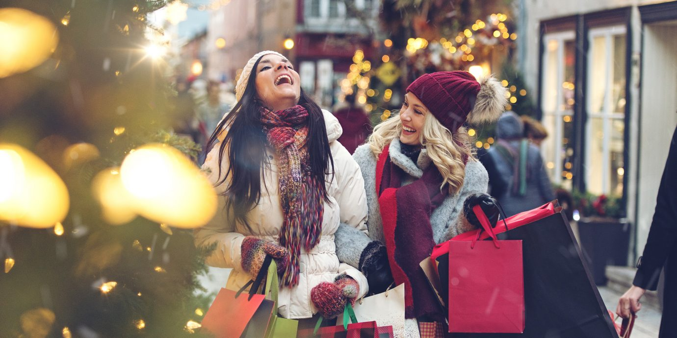 Two women holiday shopping with snow flurries