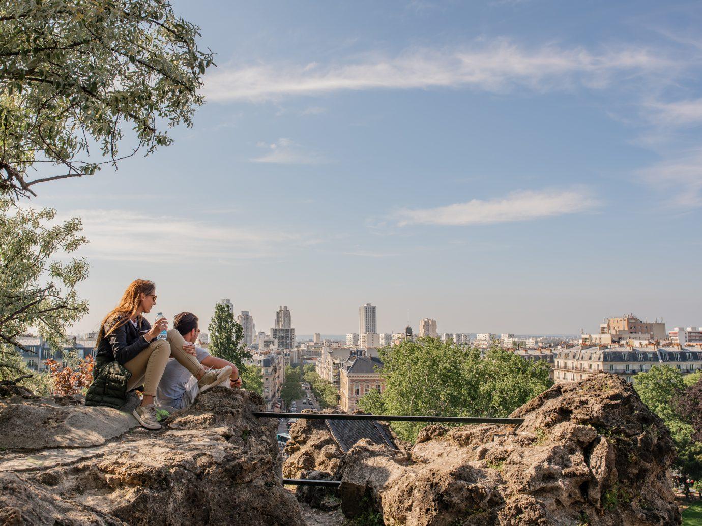 Friends climb a rock on a hill in Parc des Buttes Chaumont