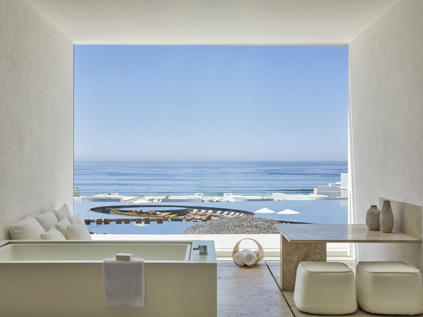 Open bathroom with a view of the ocean and pools