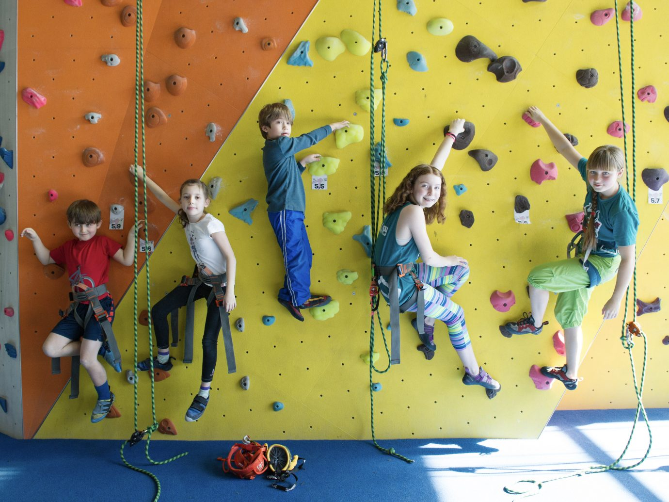 kids hanging on rock climbing wall posing for photo