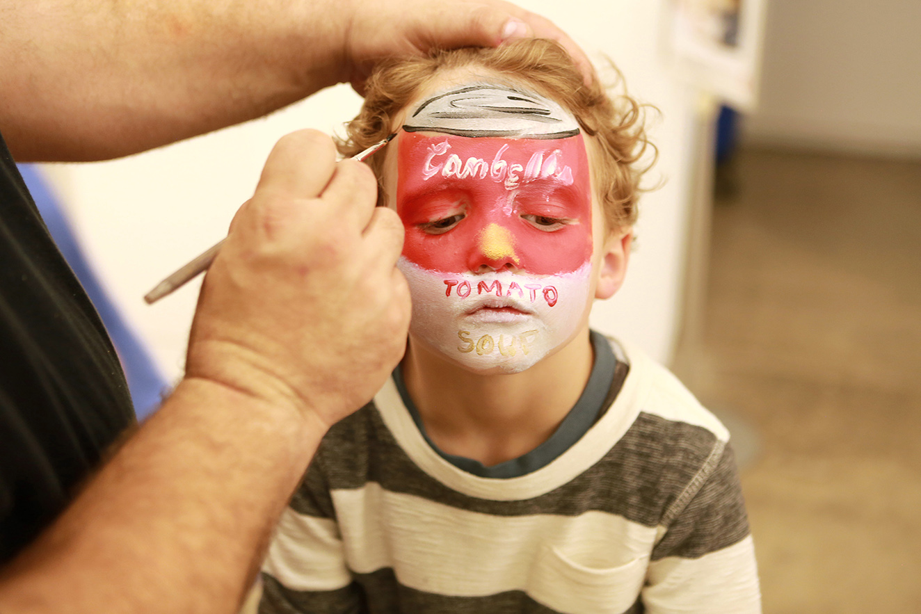 kid getting faced painted with Campbell's soup logo