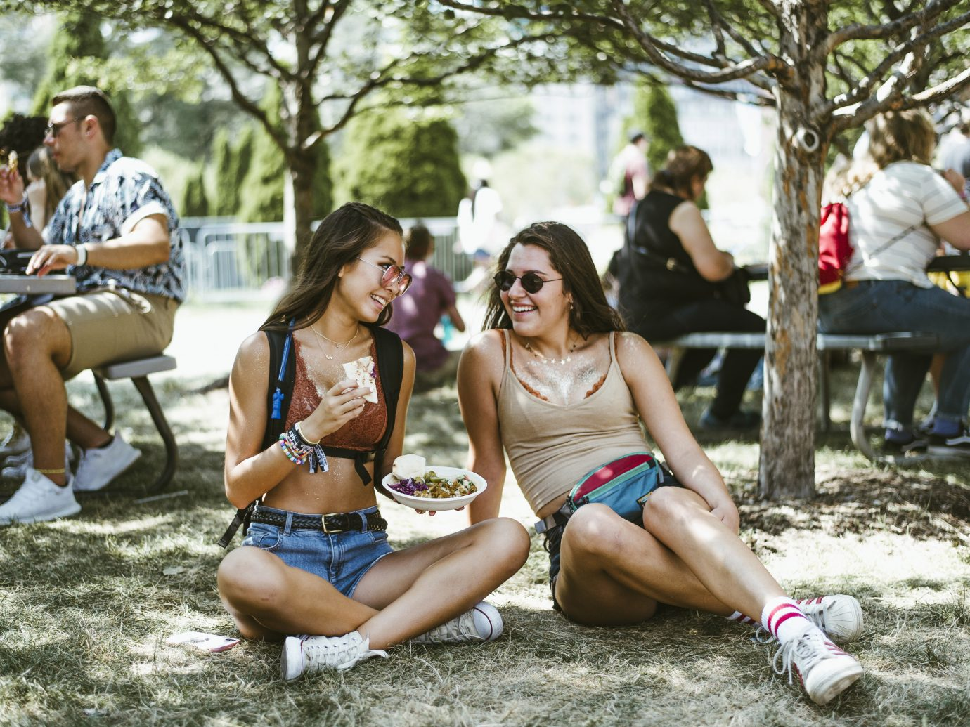 two girls eating falafel on the grass