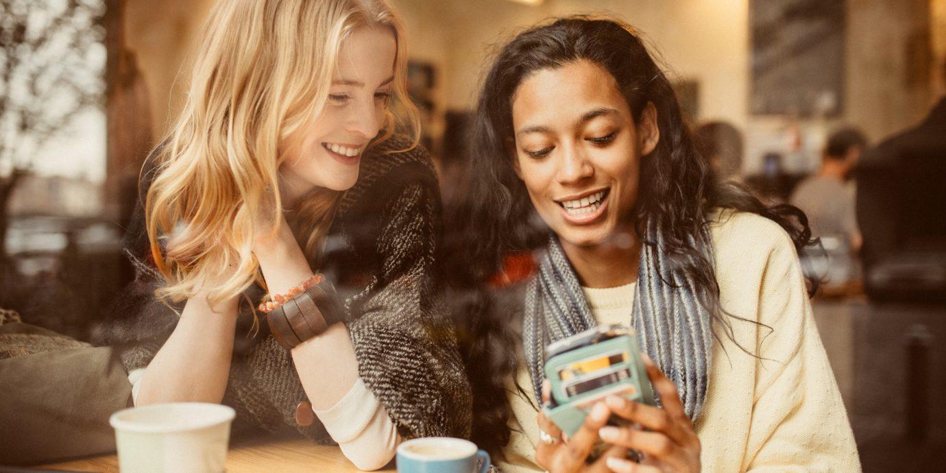 Girlfriends using Smartphone in Coffeeshop to shop online