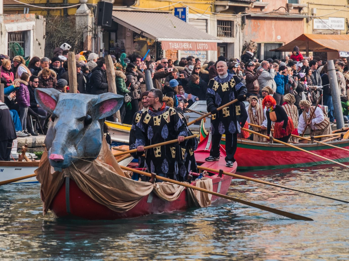 People dress up and row decorative boats in Venice