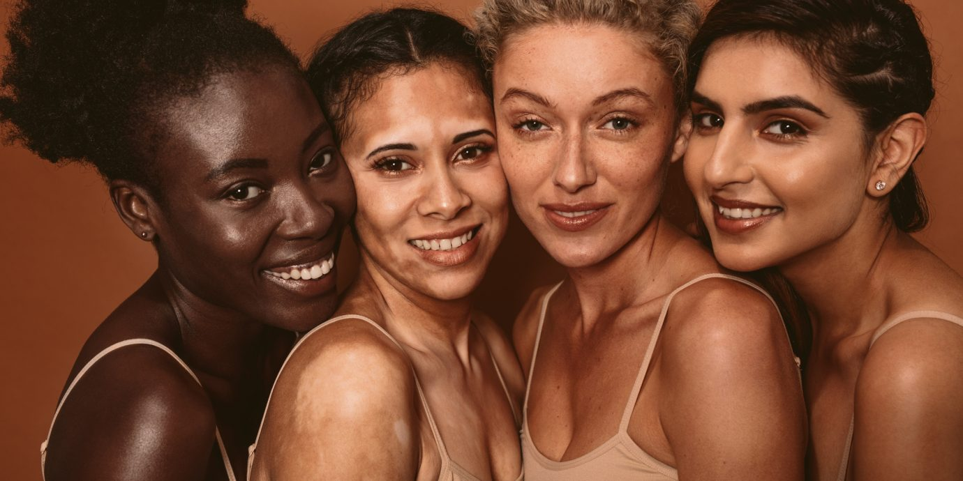 Portrait of four young women with different skin types. Diverse group of females standing together and looking at camera.