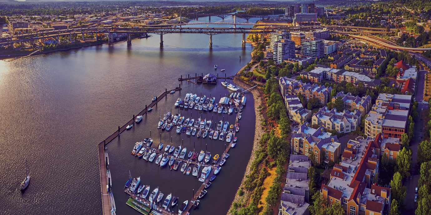 Aerial of Downtown Portland at Tom McCall Waterfront Park overlooking the Marina on early sunny morning with Tilikum Crossing Bridge in the distance