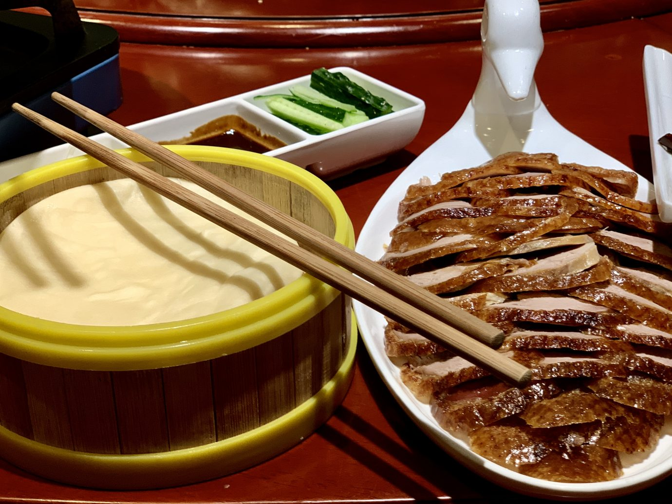 "Beijing's famed Peking Duck is sliced thin and served with rice pancakes, cucumber, onion and ""peking"" sauce."