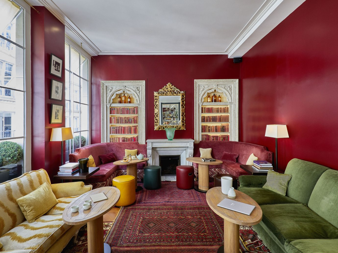interior sitting space with red walls and carpet but with numerous colorful couches