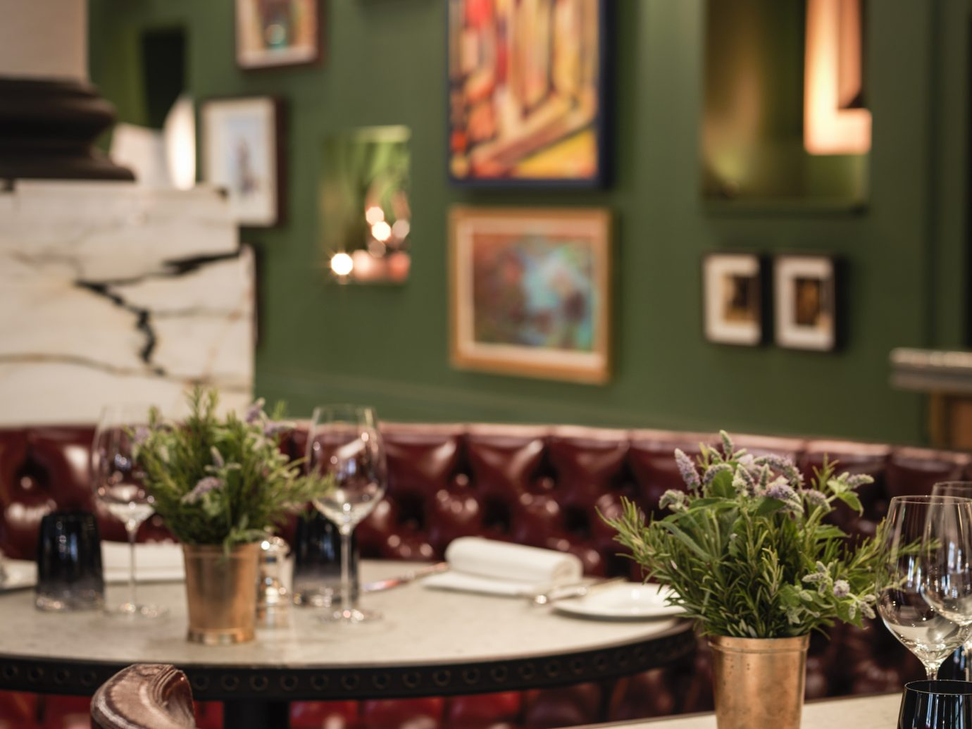 set tables with dark red leather and green walls