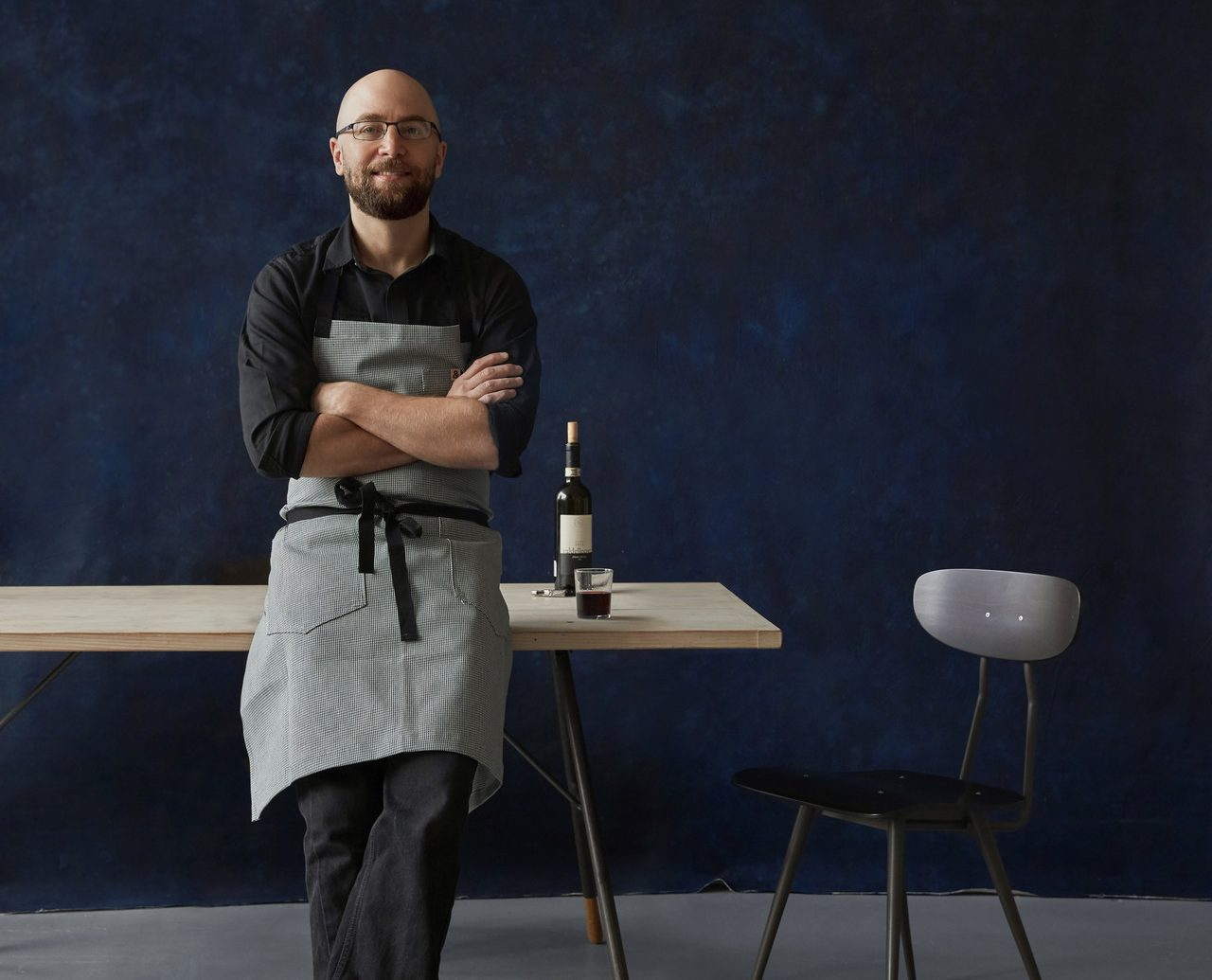 chef leaning against a table
