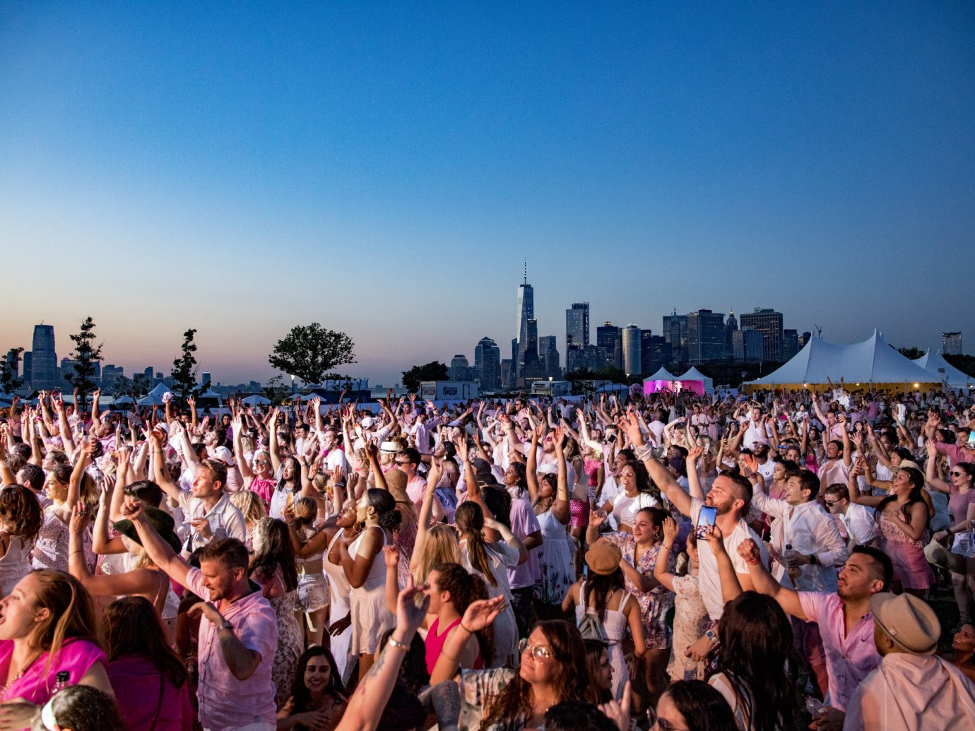 crowd of people dancing to music at dusk with NYC skyline in background