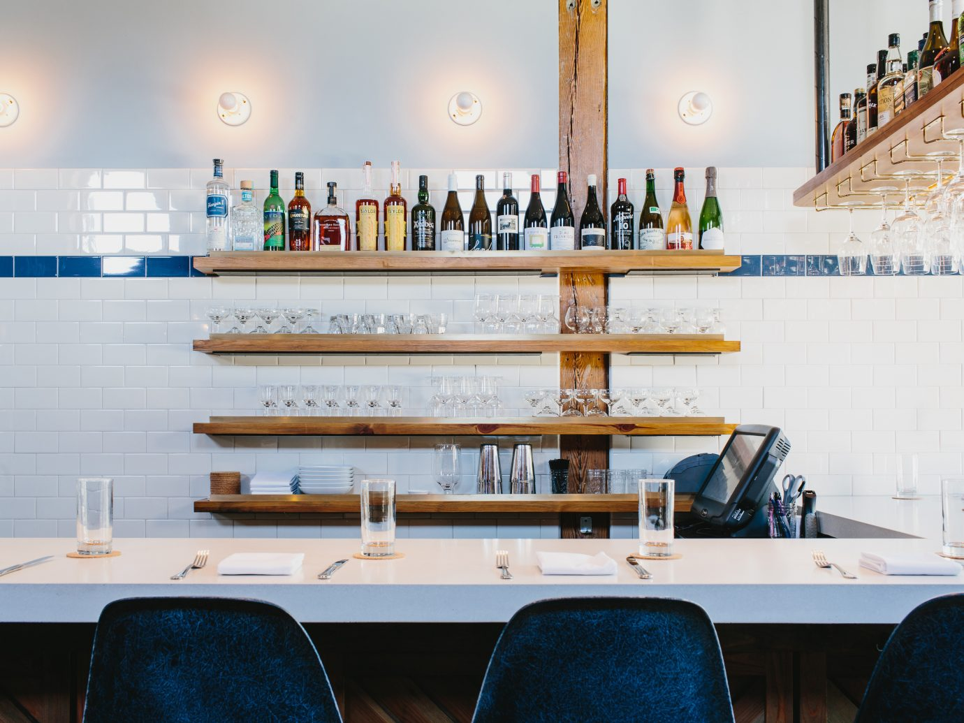 Clean white bar top with white walls and light wood shelves holding bottles