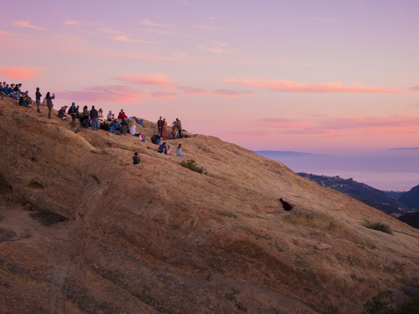 people performing and others watching during sunset on a huge rock