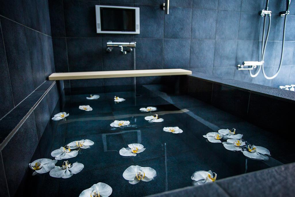 large black soaking tub with flowers floating atop