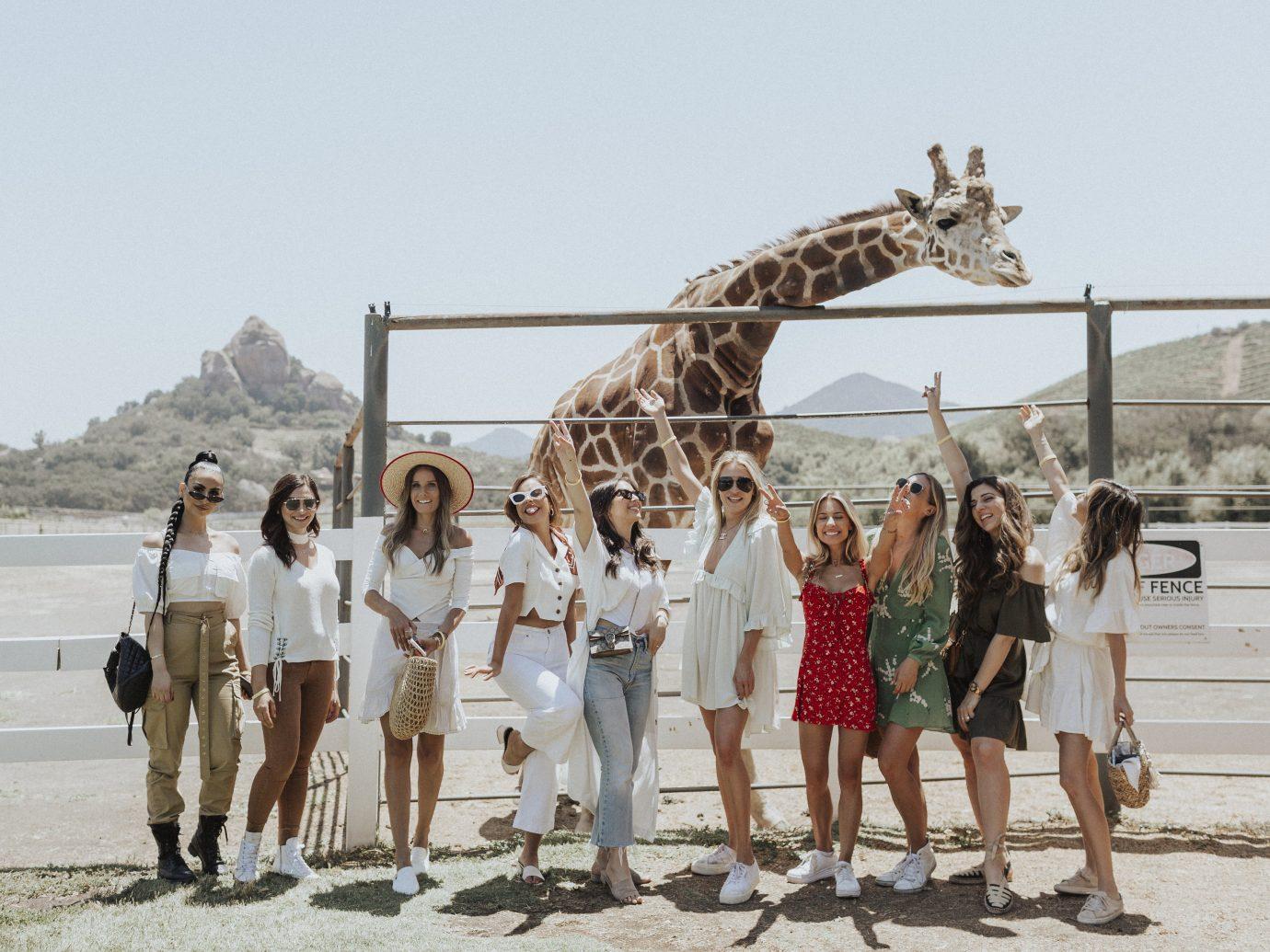 group of girls posing in front of giraffe