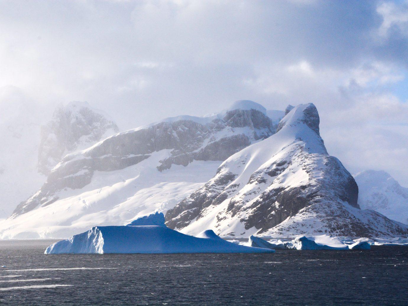 Iceberg with mountain at sunrise