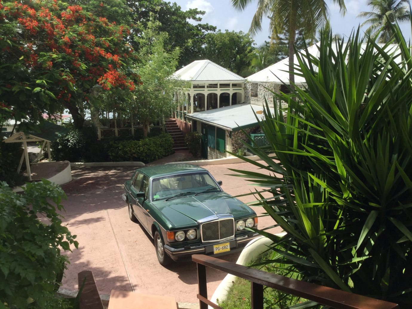 car in driveway in tropical setting