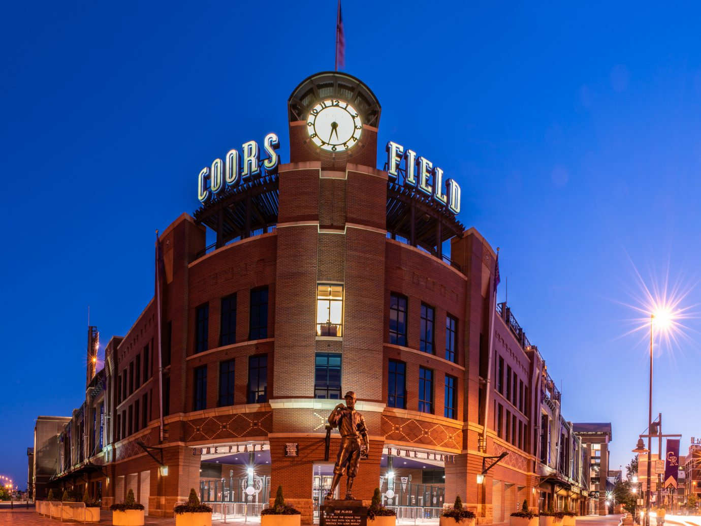 Coors Field, home of the Colorado Rockies baseball team, showing the glowing lights and vintage brick design in the early hours of a summer dawn on August 9, 2018 in Lodo, Denver.