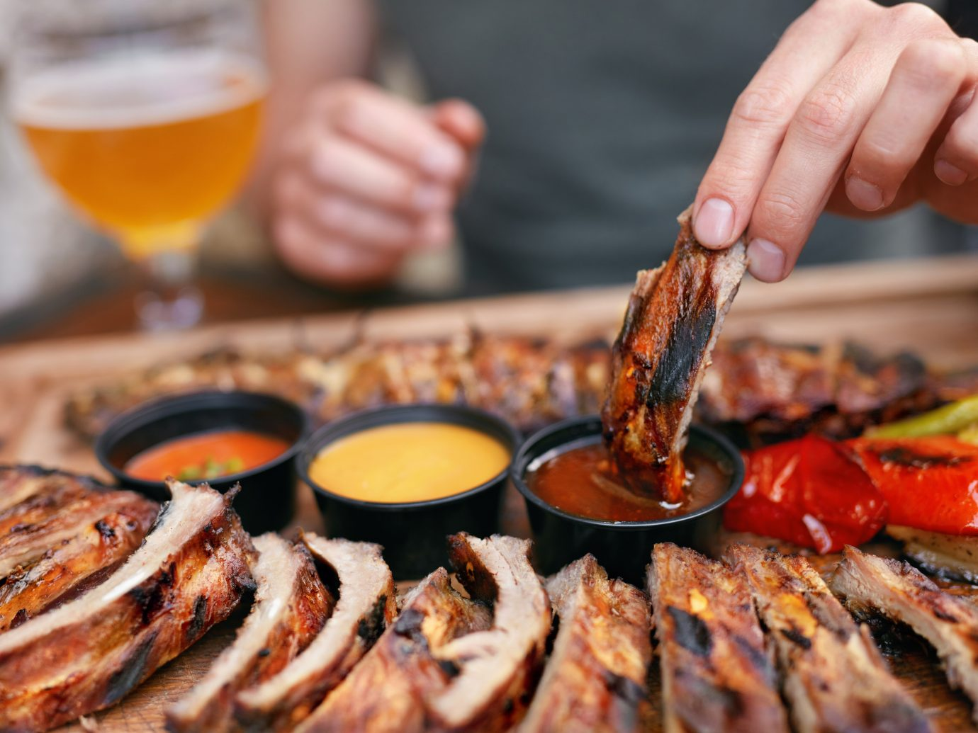 Barbecue Ribs With Sau?es Closeup. Man's Hand With Spareribs. High Resolution