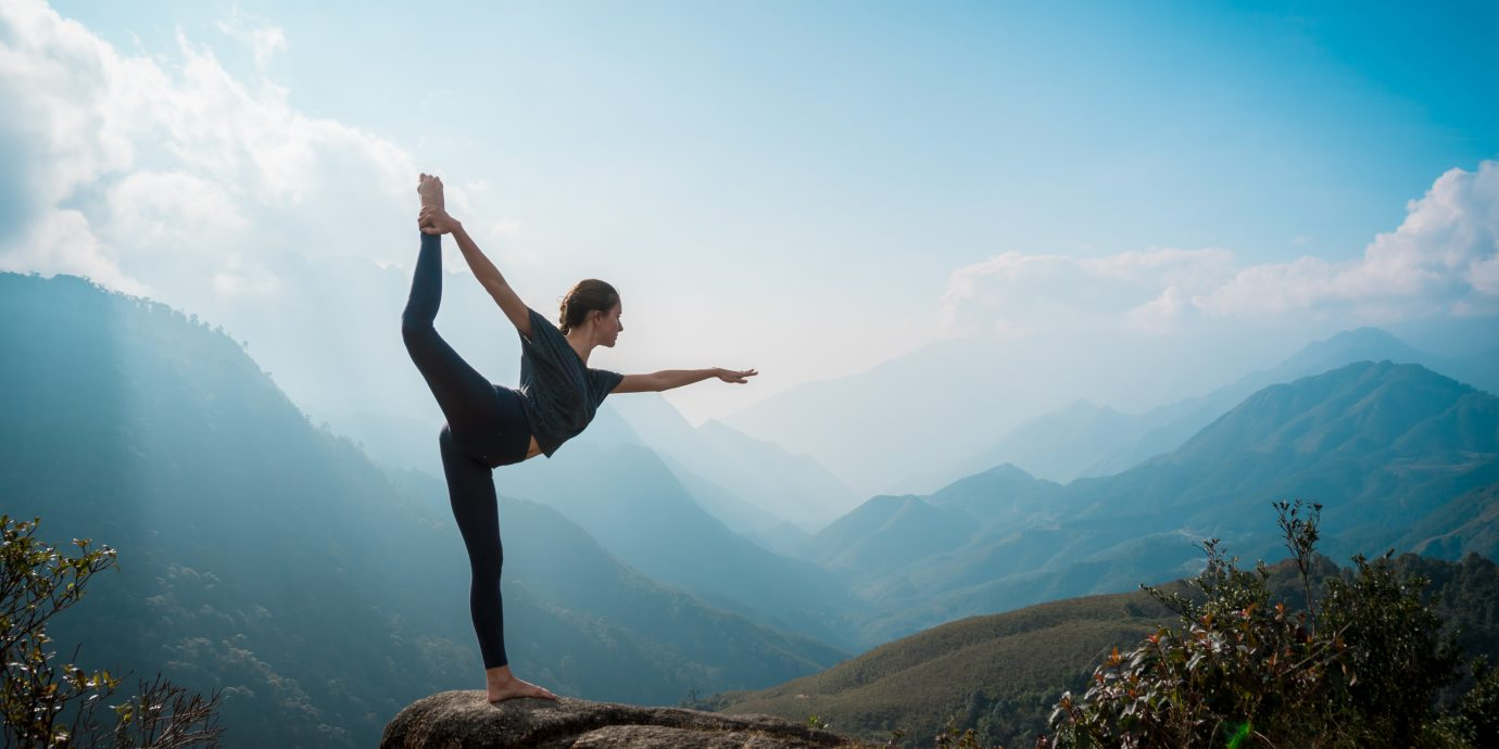 Woman training yoga at sunrise, mountains on background